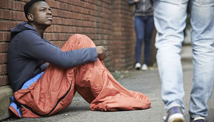 Homeless Teenage Boy BIn Sleeping Bag On The Street